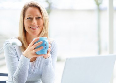 Portrait of mature business woman with a laptop and drinking cof