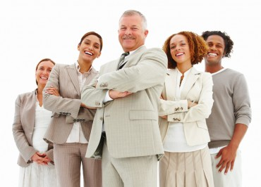 Portrait of a happy business man standing with executives agains